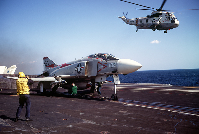 A plane director stands by as other flight deck crewmen prepare a Fighter Squadron 74 (VF-74) F-4J Phantom II aircraft for launch from the attack aircraft carrier USS AMERICA (CVA-66). A Helicopter Combat Support Squadron 2 (HC-2) SH-3 Sea King helicopter is taking off in the background