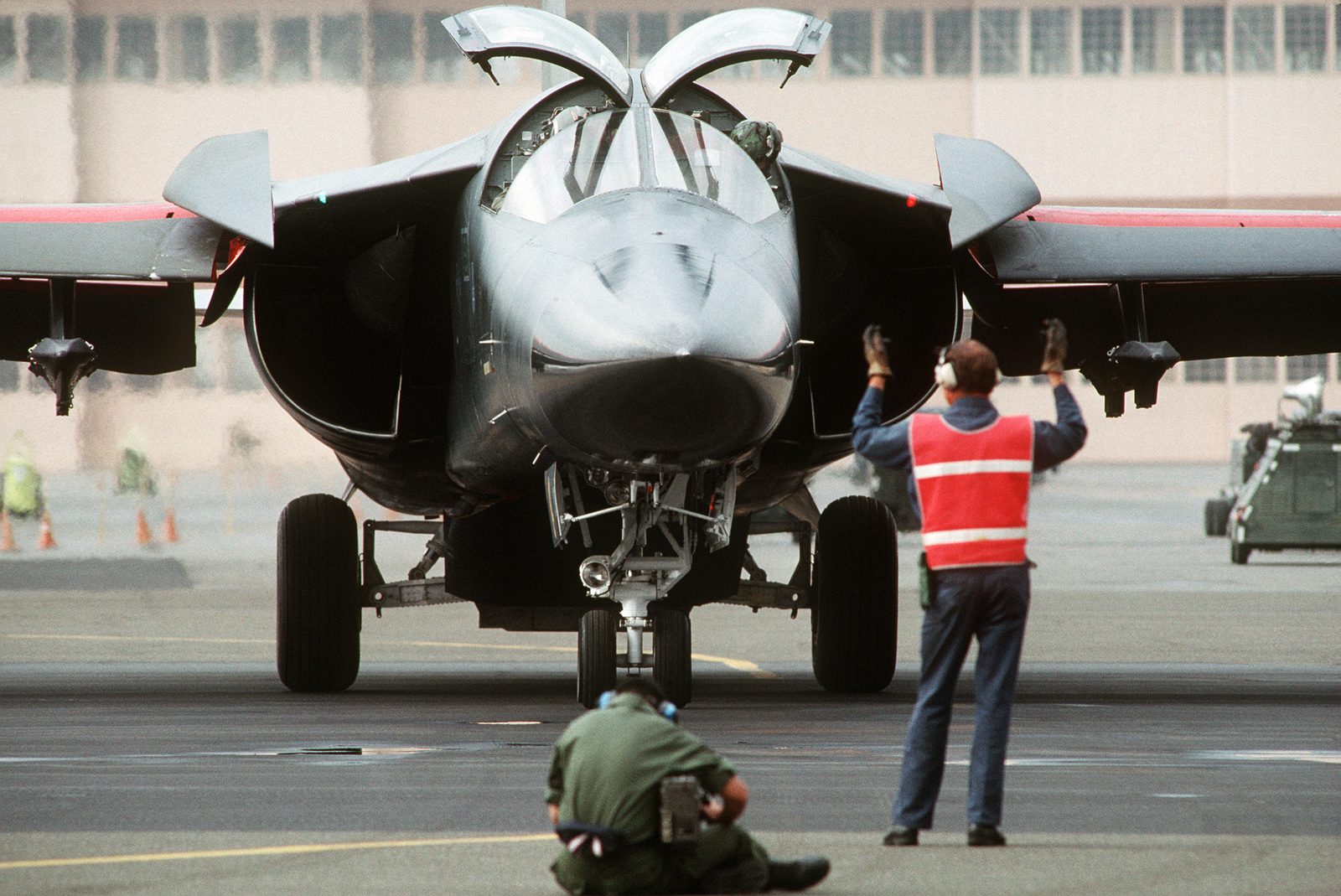 A ground crewman guides the pilot of an F-111 aircraft as it arrives on base for participation in Exercise PROUD SHIELD 87, the Strategic Air Command bombing and navigation competition