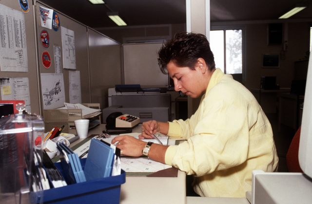 Nellie Barone, an employe of Grumman Aerospace Corp., goes over some paperwork in the corporate office. Grumman provides technical representatives to local commands and to units visiting the naval air station. These representatives help keep Navy aircraft and other equipment working properly