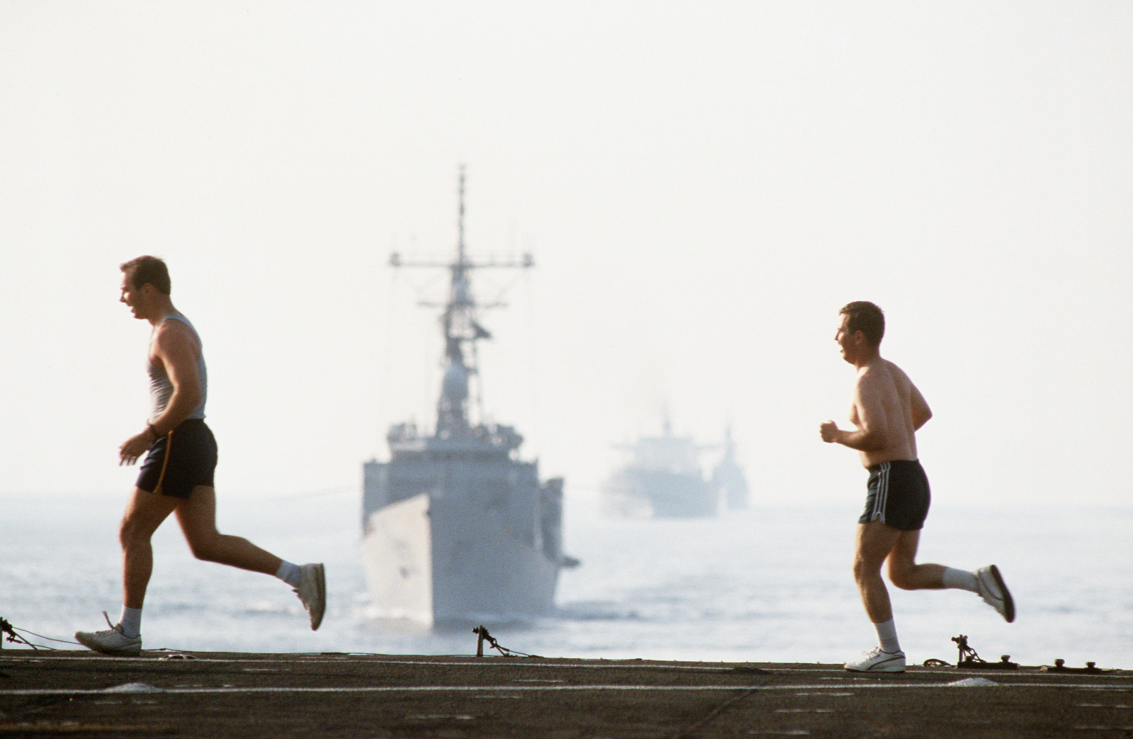 Persian Gulf.  Crew members jog along the aft edge of the deck of the amphibious transport dock USS RALEIGH (LPD 1) as it leads the guided missile frigate USS HAWES (FFG 53), the reflagged tanker GAS KING and the guided missile cruiser USS WILLIAM H. STANDLEY (CG 32) through the gulf.  The ships are part of the tanker convoy No. 12