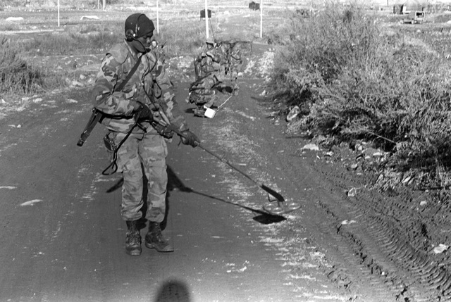 A Marine engineer clears a road of mines during the force-on-force exercise of Operation Bear Hunt '88