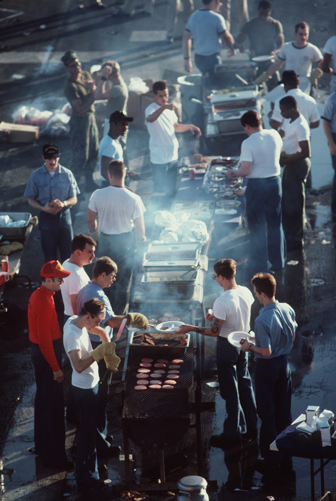 """Arabian Sea.  Crew members gather around a barbecue pit and food table on the flight deck during a""""steel beach picnic""""aboard the amphibious assault ship USS OKINAWA (LPH 3)"""