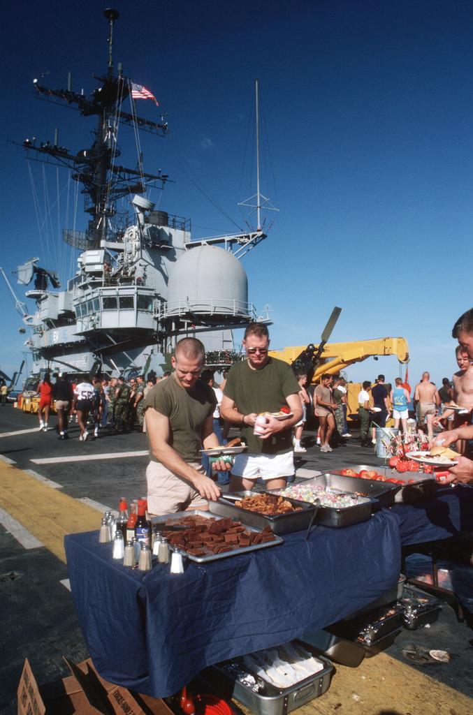 "Arabian Sea. Crew members pass through the serving line during a ""steel beach picnic"" on the flight deck of the amphibous assault ship USS OKINAWA (LPH 3)"