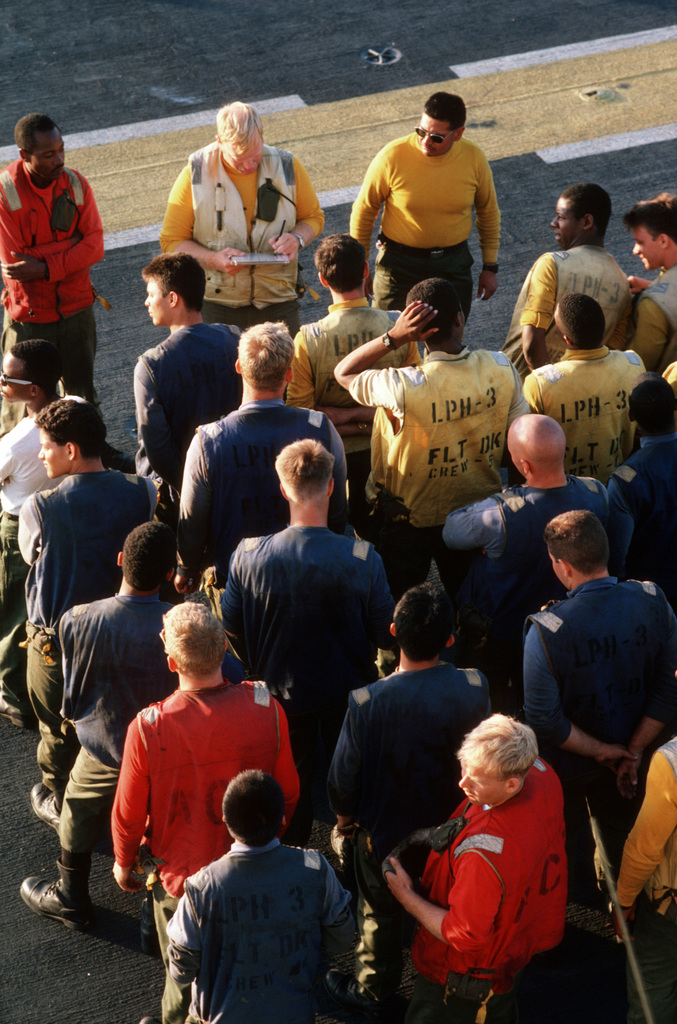 "Arabian Sea. Members of the flight deck crew muster for a cleaning detail after a ""steel beach picnic"" aboard the amphibous assault ship USS OKINAWA (LPH 3)"