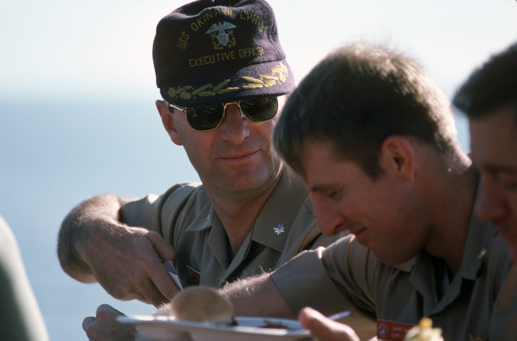 """Arabian Sea. The executive officer talks with another officer during a """"steel beach picnic"""" on the flight deck of the amphibous assault ship USS OKINAWA (LPH 3)"""