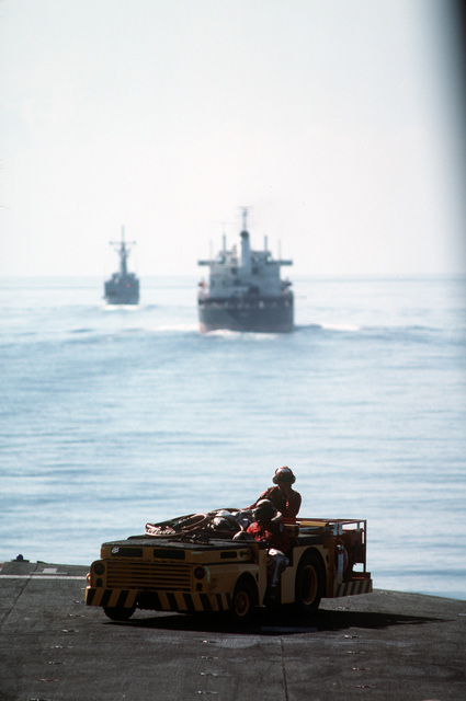 Crash crewmen stand by in an MD-3A tow tractor equipped for fire fighting during flight operations aboard boatswain's the amphibious assault ship USS OKINAWA (LPH 3). The OKINAWA is participating in a reflagged tanker escort operation