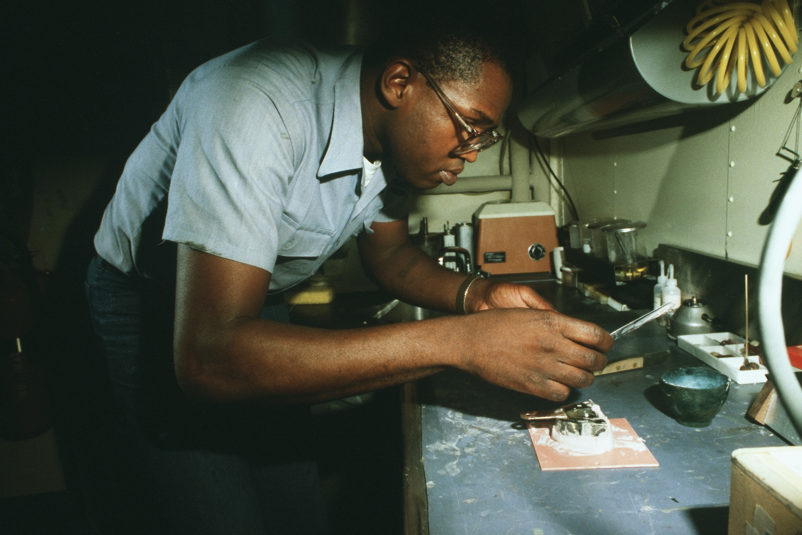 Dental Technician 1ST Class (DT1) George Allen pours an impression mold in the dental department of the battleship USS MISSOURI (BB 63)