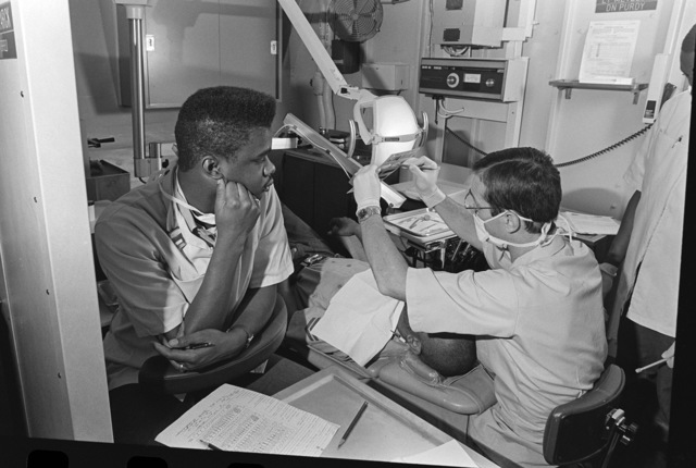 Dentalman (DN) Eric Purdy, left, records information as the dentist, Lieutenant (LT) (Dr.) David Metzler, explains an X-ray to his patient on board the battleship USS MISSOURI (BB 63)
