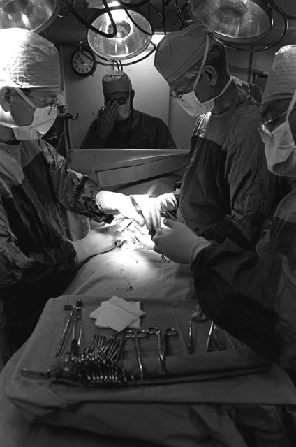 LT. (Dr.) William S. Elwood, left, and CAPT. (Dr.) Jerry Ragland, right, perform umbilical herniorrhaphy surgery in the operating room on board the battleship USS MISSOURI (BB-63). They are being assisted by LT. CMDR. John Hutchins, center, nurse anesthetist, and Hospital Corpsman 2nd Class Rodrigo Gregorio, right foreground
