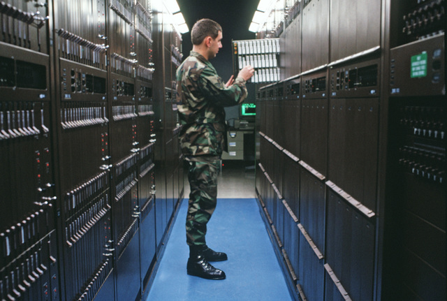 SENIOR AIRMAN (SRA) Mickey L. Mertz from the 1881st Communications Squadron removes a bad card located by the MAP-01 maintenance administration computer at the Dial Central Office Management Information System (DCOMIS) Center