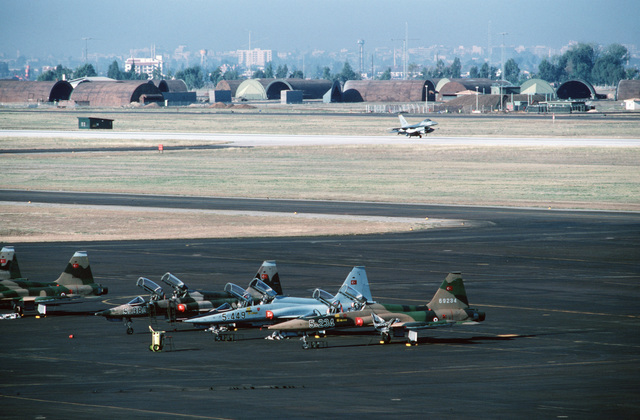 A 613th Tactical Fighter Squadron F-16A Fighting Falcon aircraft lands at the base.  Turkish air force T-38 Talon aircraft are parked on the flight line in the foreground.  Aircraft from the 613th TFS are deployed to Incirlik, one of two bases to which th