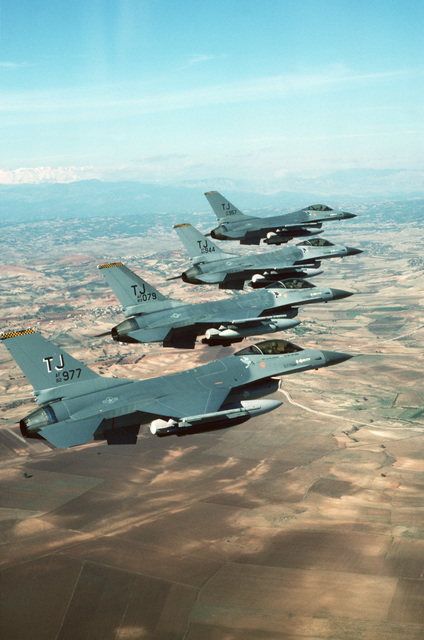 An air-to-air right side view of four 613th Tactical Fighter Squadron F-16A Fighting Falcon aircraft in echelon formation making a final approach to Incirlik Air Base, Turkey