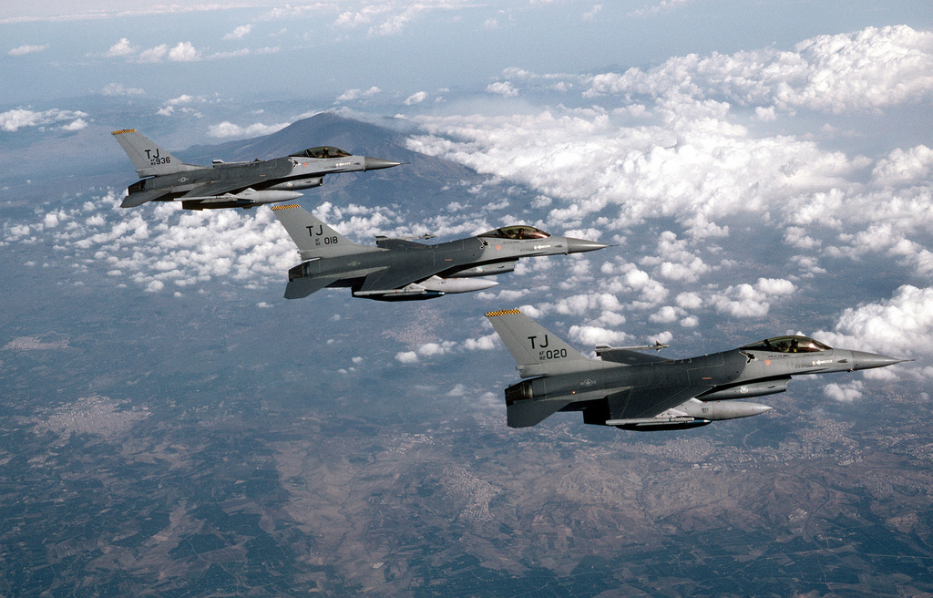 An air-to-air-right side view of three 613th Tactical Fighter Squadron F-16A Fighting Falcon aircraft flying in echelon formation near Mt. Etna. The aircraft are deploying to Incirlik Air Base, Turkey