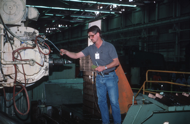 Danny L. Shelton, numerical control mill operator with McDonnell-Douglas Corp., checks the Sundstrand OM-4 milling machine which will make the first cut in the metal used on the first production C-17 aircraft