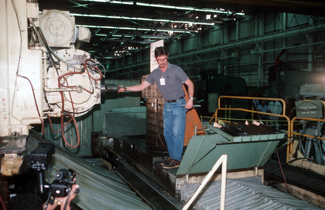 Danny L. Shelton, numerical control mill operator with McDonnell-Douglas Corp., changes the bit on the Sundstrand OM-4 milling machine which made the first cut in the metal used on the first production C-17 aircraft