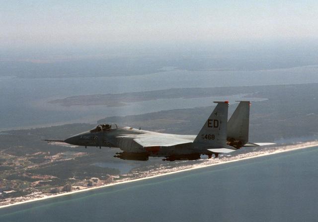 Shot of an F-15 Eagle aircraft, armed with GBU-12's, flies along the Florida coastline