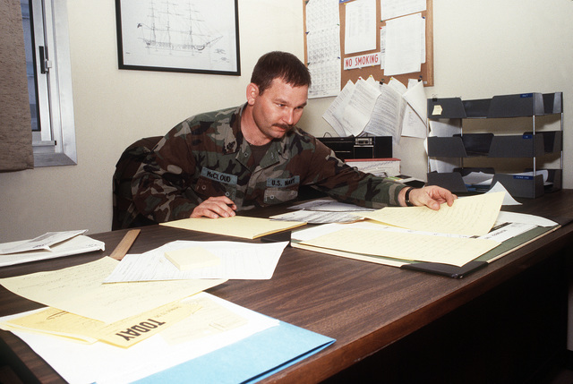 SENIOR CHIEF MASTER at Arms McCloud, assistant security officer, reviews paperwork at his desk