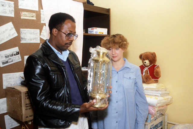William Sturdivant, a military customs inspector, checks an oil lamp purchased by AIRMAN Kimberly Candy