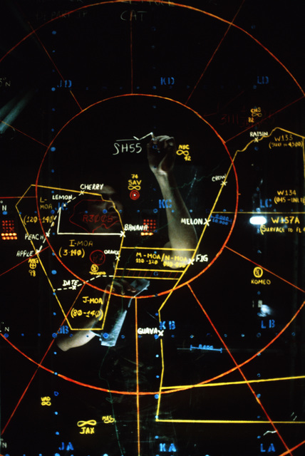 AIRMAN First Class (A1C) Rick Villanweal plots interceptor tracks on a screen inside the command center during Exercise CORONET STROKE'88.  The objectives of the exercise are to establish and maintain a netted tactical air control system, set up a composite air surveillance system, and control sorties flown by various aircraft to test their combat capabilities under difficult field conditions.  CORONET STROKE'88 represents the largest single-service netting of tactical communication in Air Force history