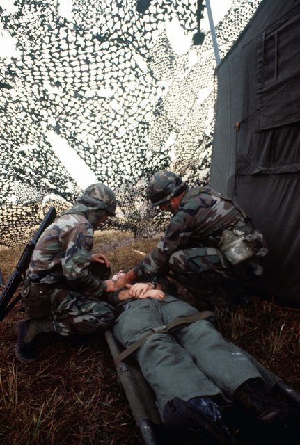SENIOR AIRMAN (SRA) Michele Adam, left, and Technical Sergeant (TSGT) Jaymes Allen give first aid to the victim of a simulated chemical attack during Exercise CORONET STROKE'88.  The objectives of the exercise are to establish and maintain a netted tactical air control system, set up a composite air surveillance system, and control sorties flown by various aircraft to test their combat capabilities under difficult field conditions.  CORONET STROKE'88 represents the largest single-service netting of tactical communication in Air Force history
