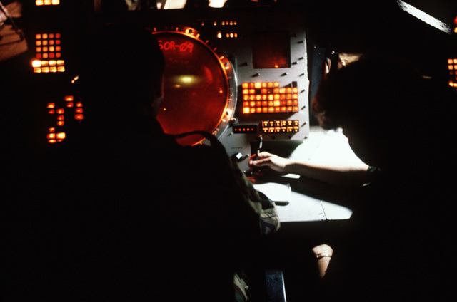 The interface control officer and control technician work on a radar scope in the message processing center during Exercise CORONET STROKE'88.  The objectives of the exercise are to establish and maintain a netted tactical air control system, set up a composite air surveillance system, and control sorties flown by various aircraft to test their combat capabilities under difficult field conditions.  CORONET STROKE'88 represents the largest single-service netting of tactical communication in Air Force history