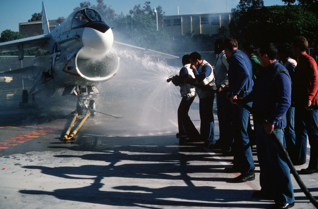 Students hose down an A-7 Corsair II aircraft during an AIRMAN apprentice program aviation firefighting lesson at the San Diego Naval Training Center.  The program provides familiarization lessons in such areas as avionics, powerplants, aviation firefighting and safety equipment