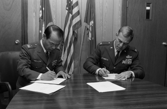 Colonel (COL) Tamio Yamashita, commander, Airborne Early Warning Group, Japan Air Self Defense Force, and COL John G. Lorber, commander, 432nd Tactical Fighter Wing, sign an E-2C Hawkeye/F-16 Fighting Falcon support agreement