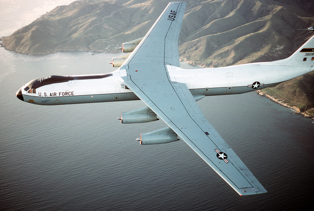 """Air-to-air, side view of a 63rd Airlift Wing's C-141B Starlifter, """"Spirit of the Inland Empire,"""" on a training mission with the Pacific coastline in the background. Exact Date Shot Unknown"""