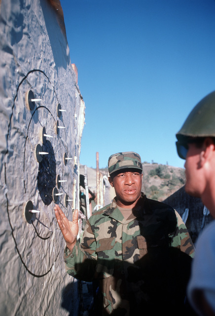Construction Mechanic 2nd Class (CM2) Eric Cambell calls for a recount on a disputed score in the target pits during M16A1 rifle qualifications for Naval Mobile Construction Battalion 4.  The battalion is participating in its annual 20-day combat field exercise