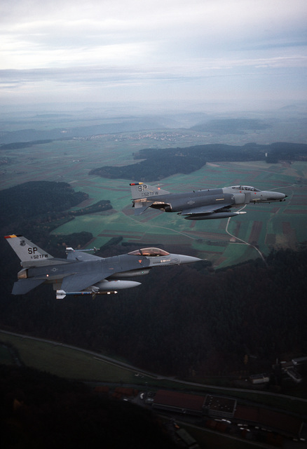 An air-to-air right side view of an F-16C Fighting Falcon aircraft, foreground, and an F-4G Phantom II Wild Weasel aircraft, both from the 52nd Tactical Fighter Wing (TFW), Spangdahlem Air Base. The F-16C is armed with AIM-9 Sidewinder missiles on the wing tips and an AGM-45A Shrike missile on the right wing pylon. The F-4G is armed with an AGM-88A High-speed Anti-Radiation Missile (HARM) on the right wing