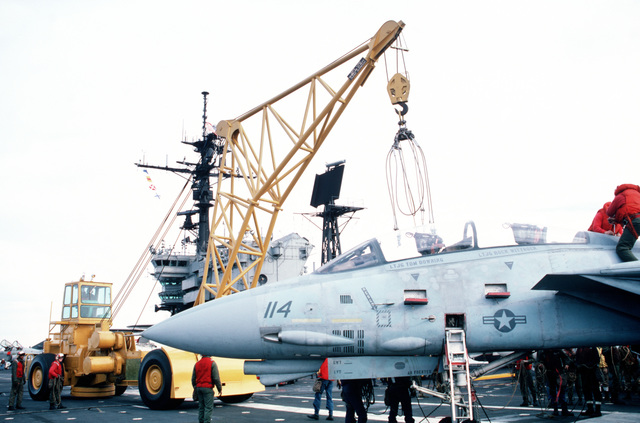 An NP-50 aircraft crane is maneuvered into position to lift an F-14 Tomcat aircraft during a general quarters drill aboard the aircraft carrier USS JOHN F. KENNEDY (CV 67)