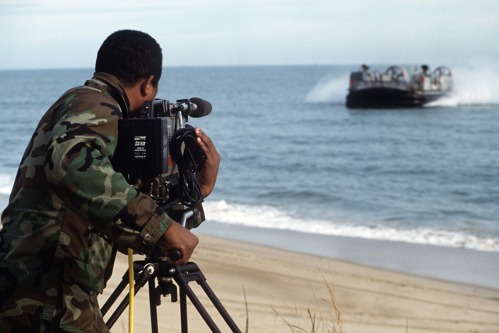 A Marine cameraman films air cushion landing craft LCAC9 as it approaches the shore near Fort Story