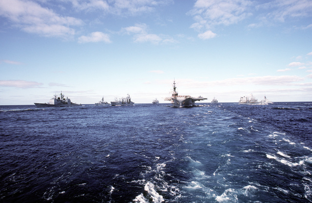 A bow view of the IOWA/MIDWAY battle group.Ships pictured are, left to right: guided missile cruiser USS TICONDEROGA (CG-47), the frigate USS FRANCIS HAMMOND (FF-1067), the fleet oiler USS CIMARRON (AO-177), the ammunition ship USNS KILAUEA (T-AE-26), the aircraft carrier USS MIDWAY (CV-41), the combat stores ship USS WHITE PLAINS (AFS-4), the fleet oiler USNS MISPILLION (T-AO-105), and the frigate USS KNOX (FF-1052)
