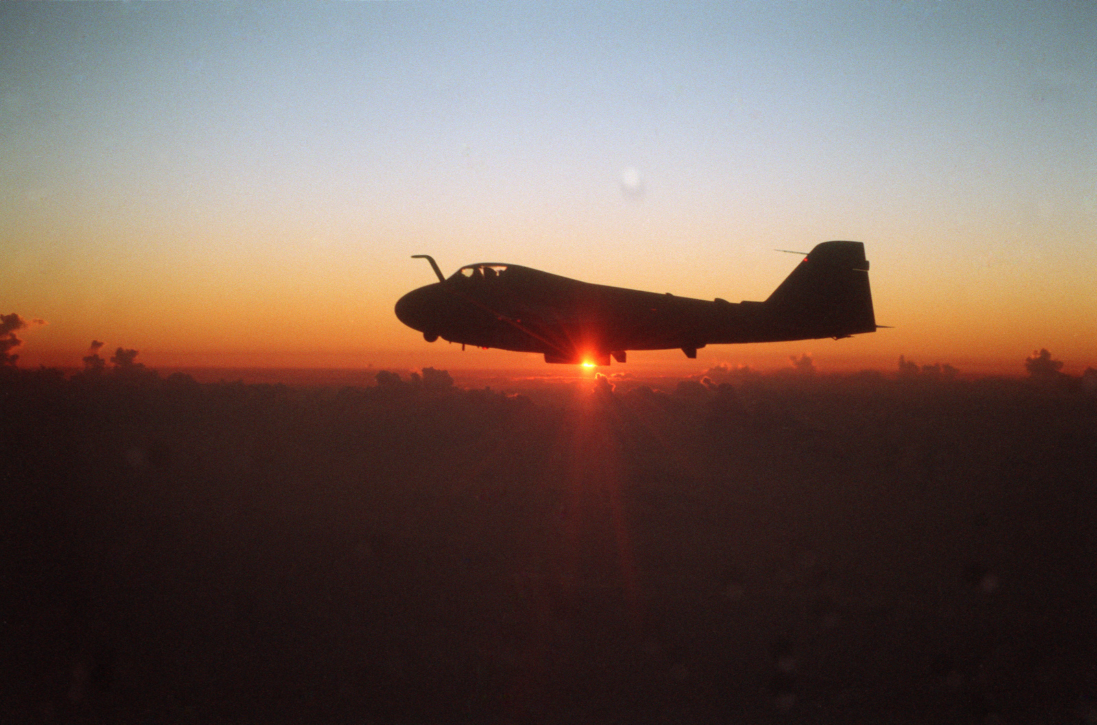 A left side view of a Marine All Weather Attack Squadron 332 (VMA(AW)-332) A-6E Intruder aircraft in flight at daybreak.  The aircraft is proceeding to Korea for Exercise TEAM SPIRIT'87