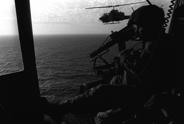 GUNNERY SGT. Mathew Whitacre mans an M-134 7.62mm minigun aboard a Marine Utility/Attack Helicopter Squadron 169 (HML/A-169) UH-1H Iroquois helicopter. Whitacre is maintaining a watch over an RH-53D Sea Stallion helicopter while on mine countermeasures patrol in the gulf