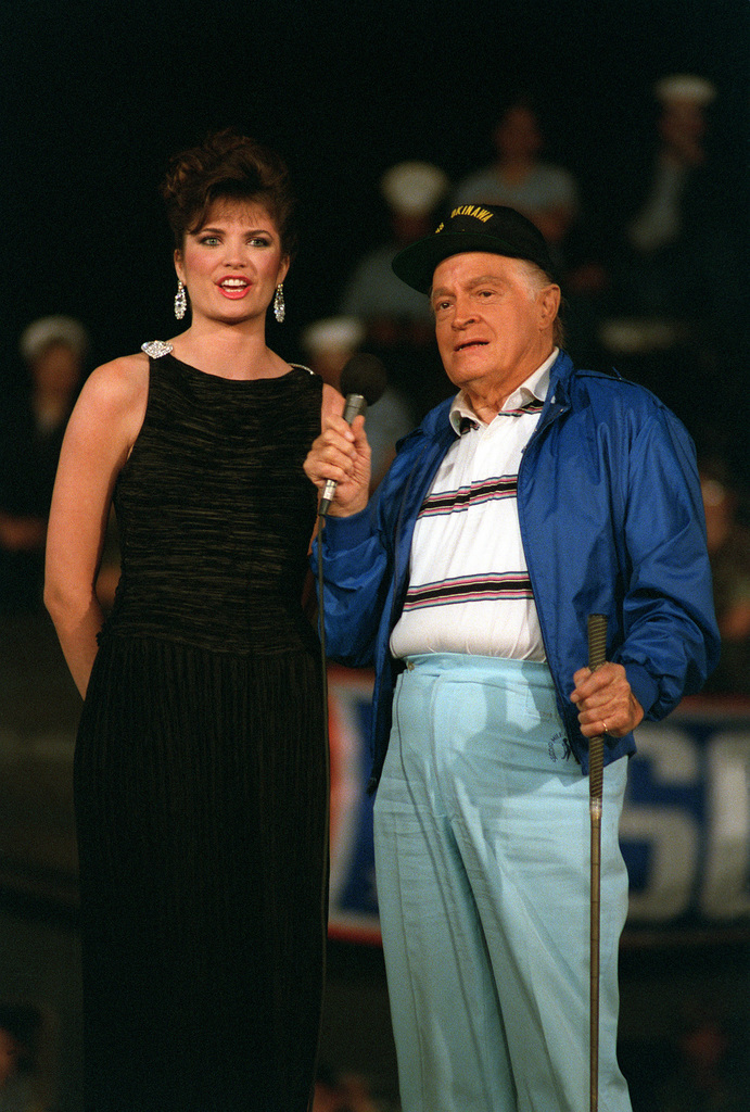Entertainer Bob Hope clowns with Michelle Royer, Miss USA, during his United Services Organization (USO) show aboard the amphibious assault ship USS OKINAWA (LPH-3)