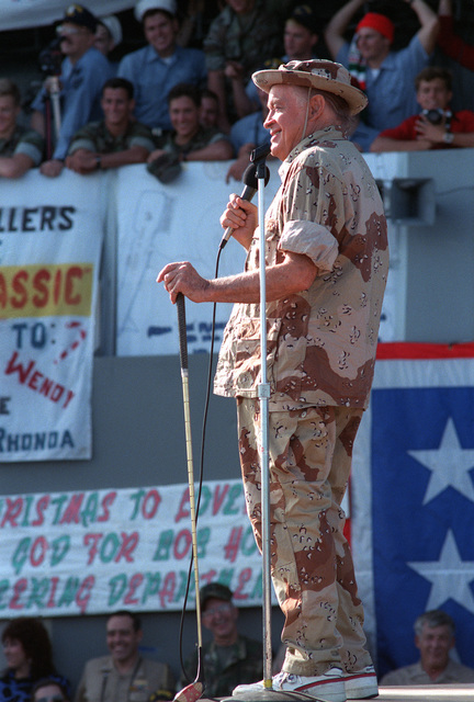 Entertainer Bob Hope, dressed in desert camouflage fatigues, during a United Services Organization (USO) show aboard the amphibious assault ship USS OKINAWA (LPH-3)