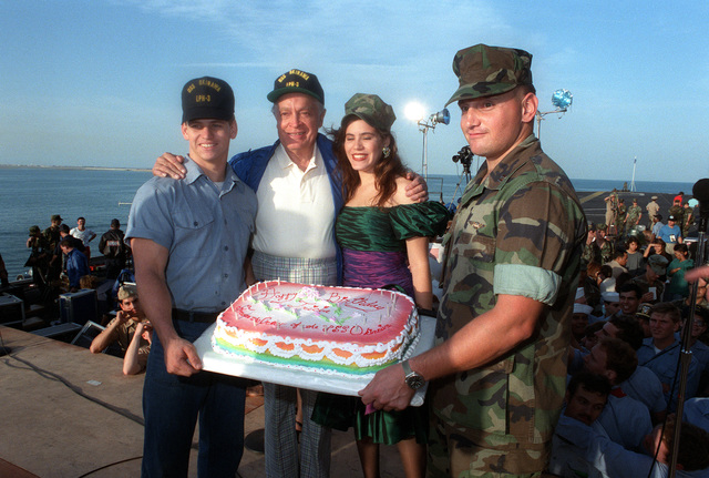 Members of the crew of the amphibious assault ship USS OKINAWA (LPH-3) and entertainer Bob Hope present Tricia Lee Fisher, daughter of singer Connie Stevens, with a birthday cake during the Bob Hope United Services Organization (USO) show