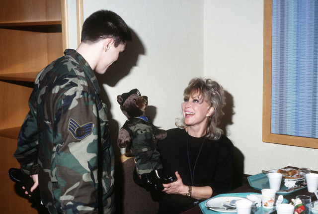 A member of the 40th Security Police presents actress Barbara Eden with a gift during her stopover on base.  Eden has been performing in Bob Hope's Christmas Show in the Persian Gulf