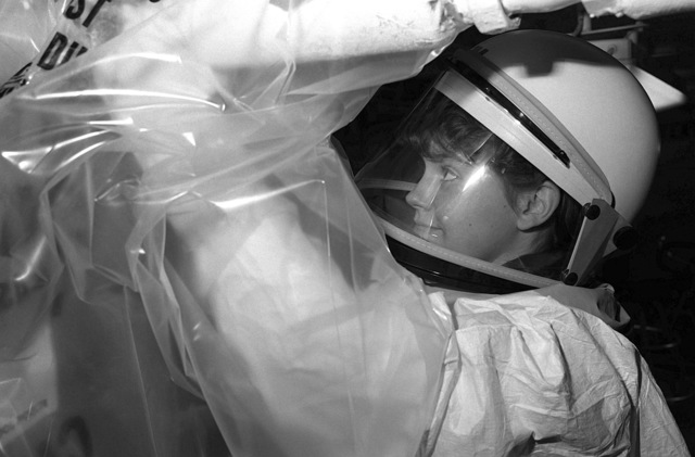 Hull Maintenance Technician 3rd Class Becky Hendricks, wearing a protective suit, removes asbestos insulation from a steam pipe aboard the destroyer tender USS SAMUEL GOMPERS (AD-37). The ship is underway off the coast of Baja, Mexico