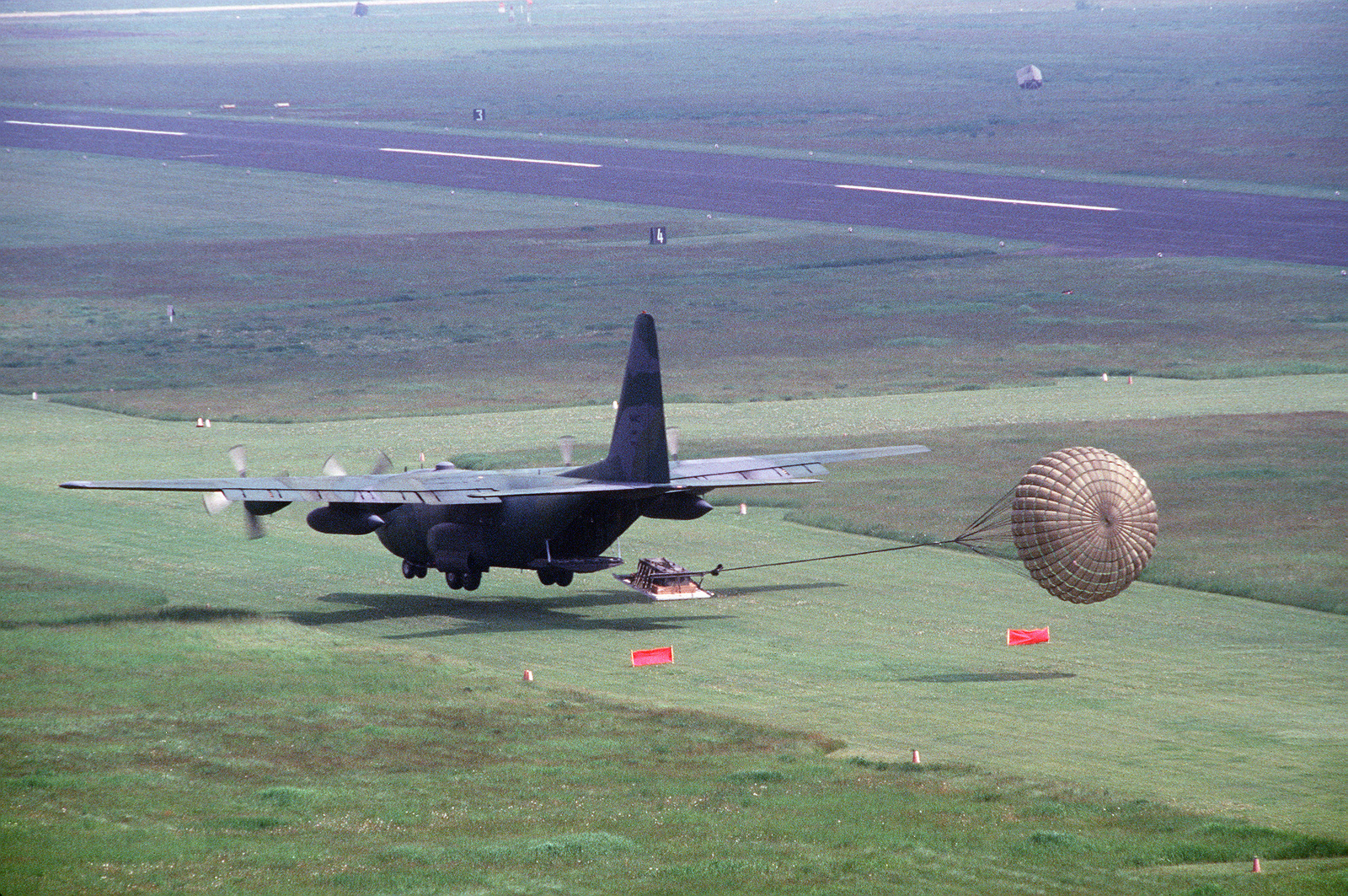 A 37th Tactical Airlift Squadron C-130E Hercules aircraft delivers cargo by a low altitude parachute extraction system (LAPES) airdrop at Templehof Central Airport during a demonstration