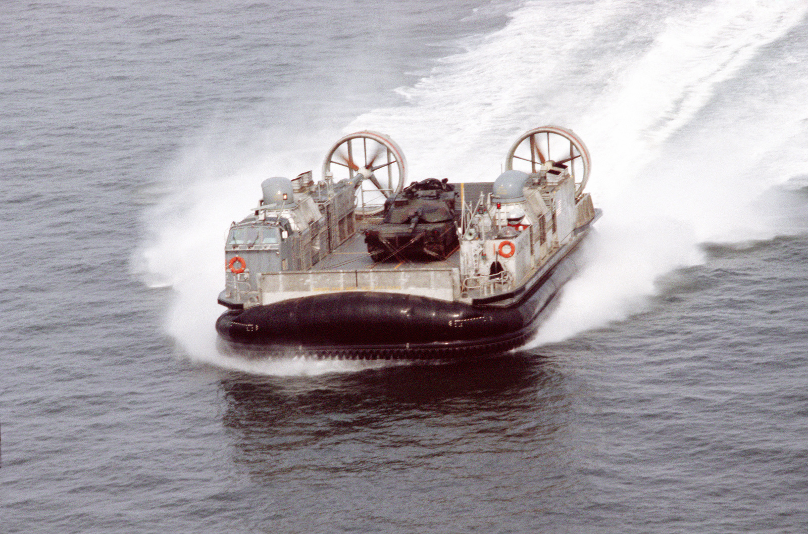 A bow view of air cushion landing craft LCAC 12 underway near Naval Amphibious Base, Little Creek, Virginia.  The landing craft is carrying a Marine M1A1 main battle tank