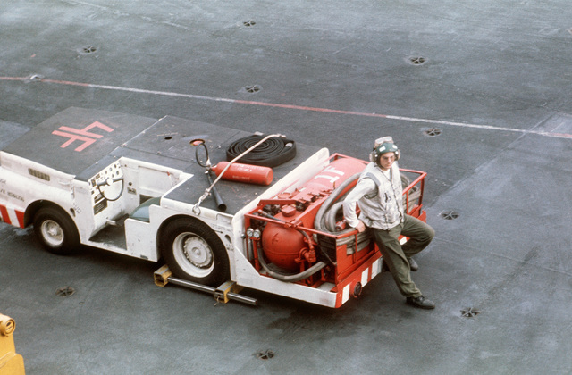 A crewman stands by with an MD-3A tow tractor converted for fire fighting on the flight deck of the aircraft carrier USS AMERICA (CV 66)