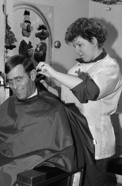 A customer at the station's barber shop flashes a smile as he sits for a haircut