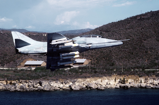 A Fleet Composite Squadron 10 (VC-10) TA-4J Skyhawk aircraft flies past part of Naval Base, Guantanamo Bay, Cuba. The Skyhawk is armed with AIM-9 Sidewinder missiles and Mark 20 cluster bombs