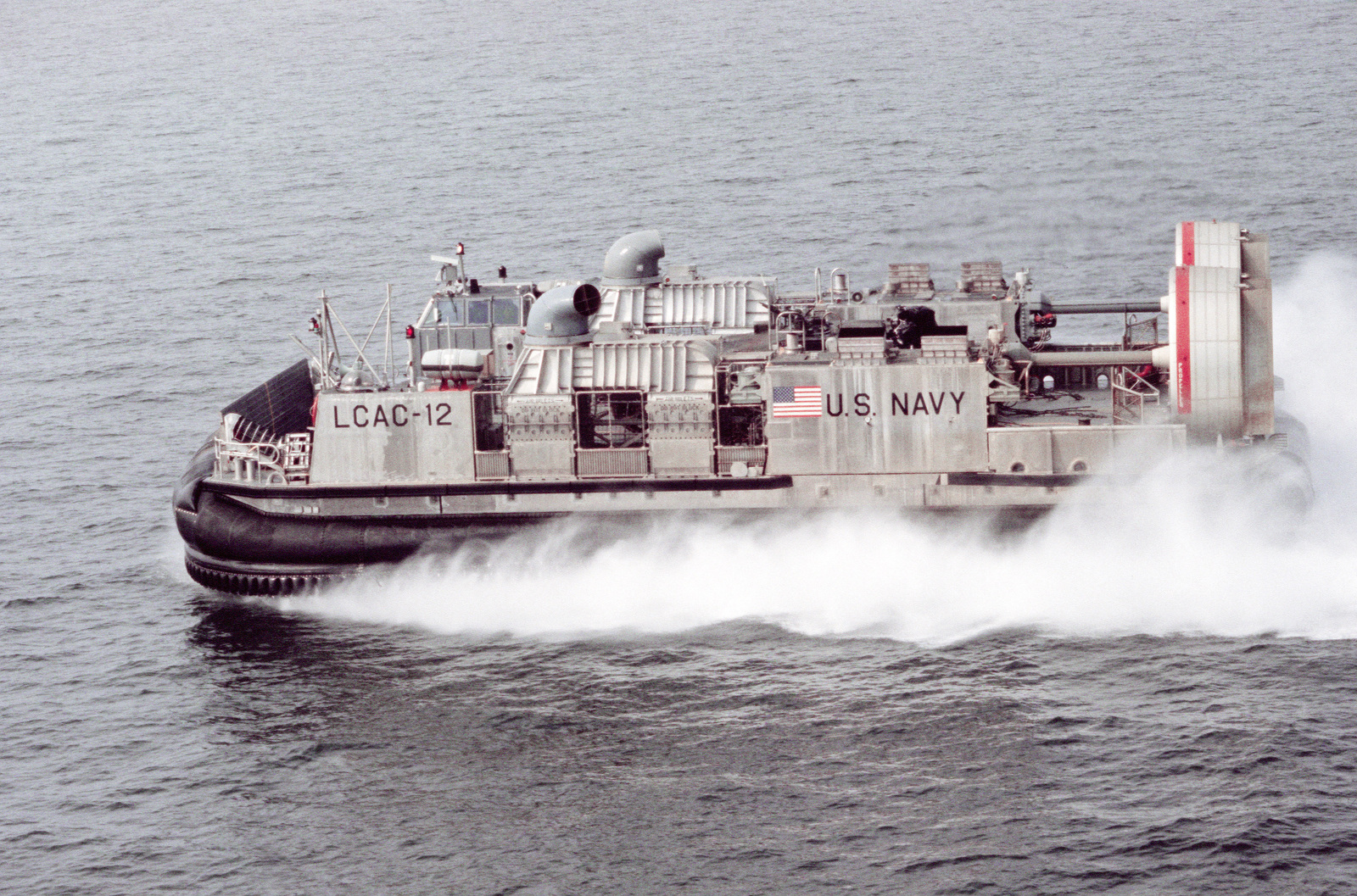 A port side view of air cushion landing craft LCAC 12 underway near Naval Amphibious Base, Little Creek, Virginia.  The landing craft is carrying a Marine M1A1 main battle tank