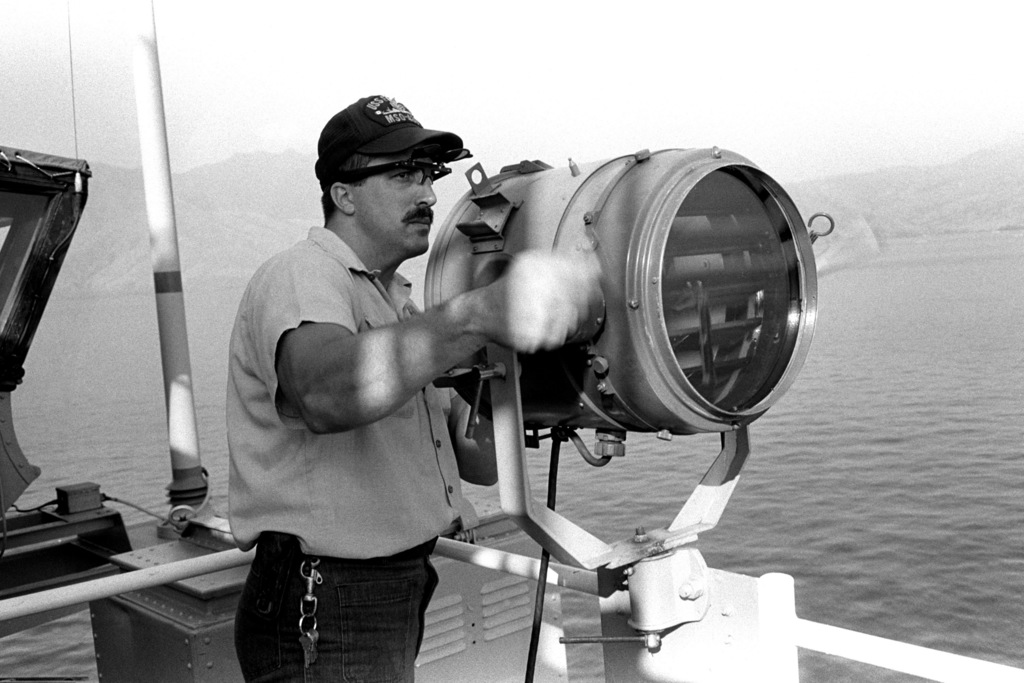 A Sailor aboard the ocean minesweeper USS ESTEEM (MSO 438) sends a message to another ship with a signal light during minesweeping operations