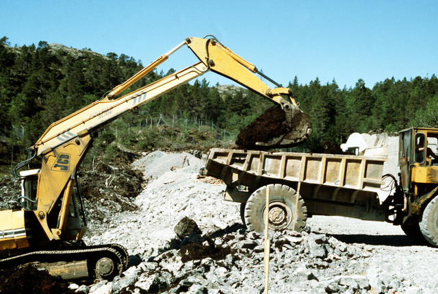 A shovel deposits backfill in a dump truck at a construction site. Civilian employees are constructing entryway to pre-positioning caves which will be used to store U.S. Marine Corps equipment