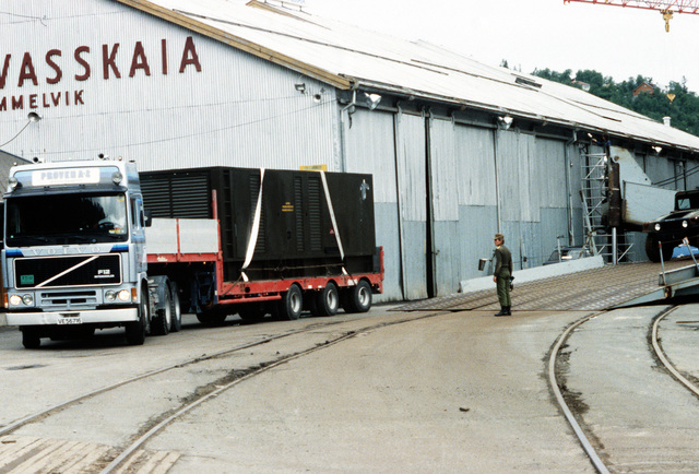 A truck transporting containers, part of a shipment of U.S. Marine Corps equipment, moves out from the dock following delivery of the cargo. The containers will be taken to pre-positioning caves for storage
