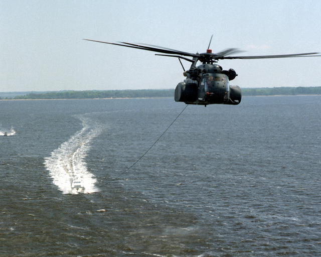 An air-to-air front view of an MH-53E Sea Dragon helicopter towing a minesweeping platform